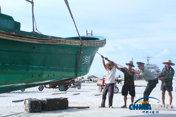 图为在三沙市永兴岛西渔码头三沙市永兴边防派出所民警正与渔民小心翼