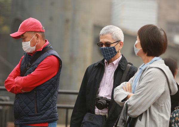 雾霾笼罩北京城区 行人戴口罩出行
