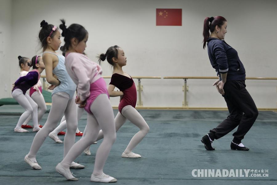 易娟老师(右)给孩子们示范舞蹈动作.(中国日报记者魏晓昊 摄)