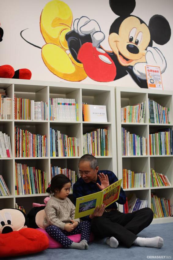 2015年4月2日,北京一处悠贝亲子图书馆内,3岁的孙佳彤在爷爷陪伴下读书。中国日报记者 王敬 摄 2015年4月2日是国际儿童图书日,北京一处悠贝亲子图书馆内,许多小朋友在家人的陪伴下读书,共享阅读的乐趣。
