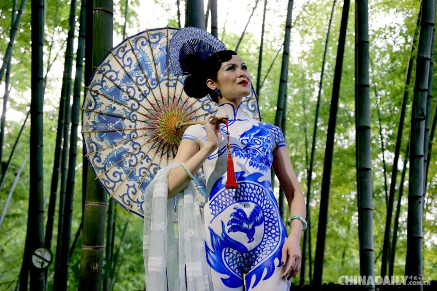 6月20日,一名模特在黄山芙蓉谷风景区上演《青花旗袍》人体艺术彩绘.