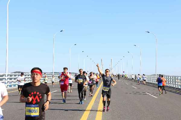 /enpproperty--> 参赛选手奔跑在长山大桥上(摄影 杨淑革) 9月4日上午7时,由大连市体育局和长海县人民政府主办的海洋岛2015首届大连长山群岛马拉松在长海县政府广场鸣枪起跑。2000名国内外马拉松爱好者参赛。经过激烈角逐,来自沈阳的选手王洋以2小时56分45秒夺得男子组第一名,大连选手孟文以3小时29分28秒夺得女子组第一名。 据了解,这是国内首个海岛环岛马拉松赛,已经在国家田径协会完成注册。赛事突出海岛特色,沿线风光秀丽,设全程马拉松、半程马拉松、10公里健康跑三个比赛项目,其中全程